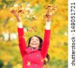 Autumn / fall woman happy throwing leaves up in the air with arms raised up towards the sky with smiling cheerful, elated expression of happiness. Beautiful girl in colorful forest foliage outdoor. - stock photo