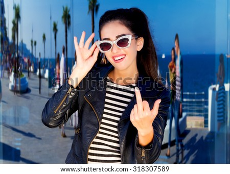 Autumn fashion close up portrait of gorgeous brunette swag sexy girl wearing black leather coat and vintage sunglasses going crazy,showing middle finger.Fashion hipster girl at amazing sea background - stock photo