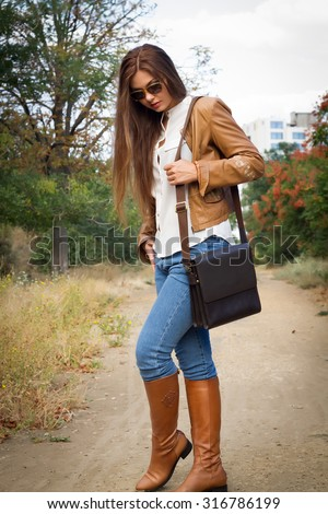 Autumn fashion image of young woman  walking in the park,wearing leather coat,white blouse,jeans and bag.Fashion urban young woman living city lifestyle walking in leather jacket,full length. - stock photo