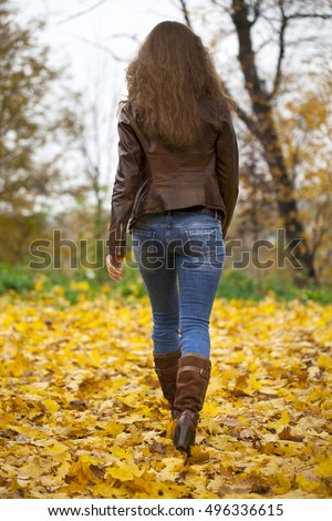 Autumn fashion image of young woman walking in the park, wearing leather jacket and blue jeans