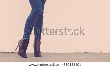 Autumn fashion outfit. Fashionable woman long legs in denim pants black stylish high heels shoes outdoor on street - stock photo
