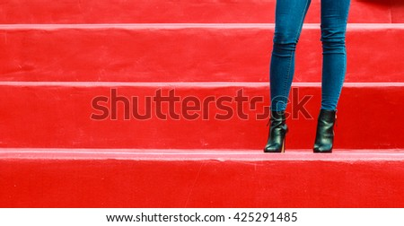Autumn fashion outfit. Fashionable woman long legs in denim pants black stylish high heels shoes outdoor on red steps - stock photo