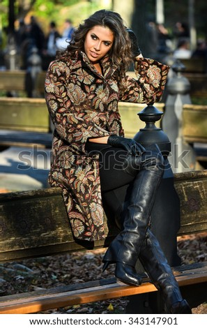 Autumn fashion portrait of young woman sitting on bench wearing elegant coat and high heel boots. - stock photo