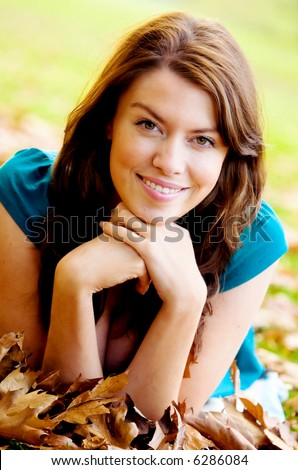 autumn female portrait on the floor looing very relaxed and smiling - stock photo