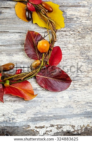 autumn floral wreath on rustic wooden background - stock photo