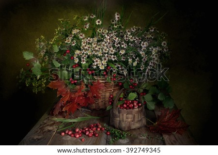 Autumn flowers and cranberry red in a wicker basket. - stock photo