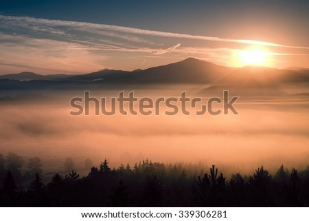 Autumn fog and clouds above freeze  mountain valley, hilly landscape
