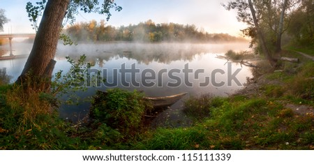 Autumn fog over the river, the sun shines the wood on shore, outdoors - stock photo