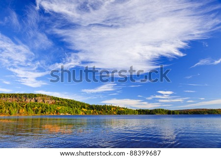 Autumn forest and lake with dramatic sky in Algonquin Park, Canada