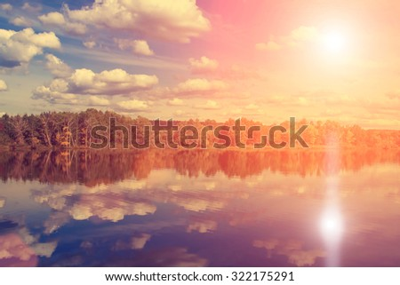 Autumn forest, clouds reflected in a lake - stock photo