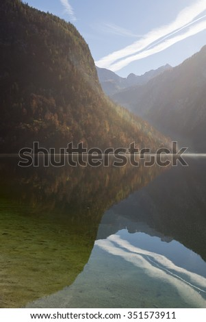 Autumn forest reflected in the smooth lake Koenigssee in the Berchtesgaden mountains and National Park