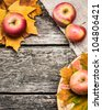 Autumn frame from apples and leaves on old wooden table. Thanksgiving day concept - stock photo
