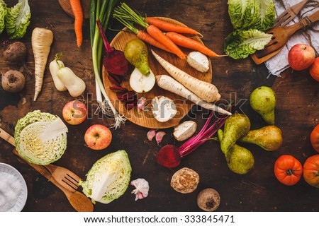 Autumn fruit and roots veggies background. Healthy, garden local produce. Rustic dark style. Horseradish, leeks, beetroot, parsley roots, celery plants, apple, pear.    - stock photo