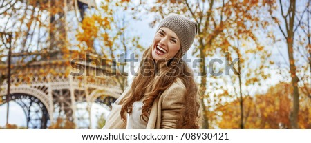 Autumn getaways in Paris. Portrait of happy young woman near Eiffel tower having fun time