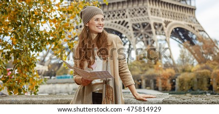 Autumn getaways in Paris. smiling young tourist woman on embankment near Eiffel tower in Paris, France holding map and looking aside