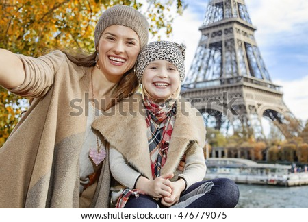 Autumn getaways in Paris with family. smiling mother and daughter tourists on embankment near Eiffel tower in Paris, France taking selfie