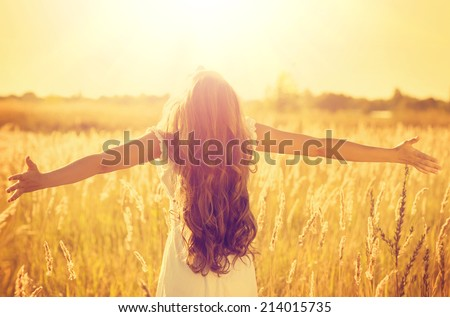 Autumn Girl enjoying nature on the field. Beauty Girl Outdoors raising hands in sunlight rays. Beautiful Teenage Model girl in white dress running on the Field, Sun Light. Glow Sun. Free Happy Woman - stock photo