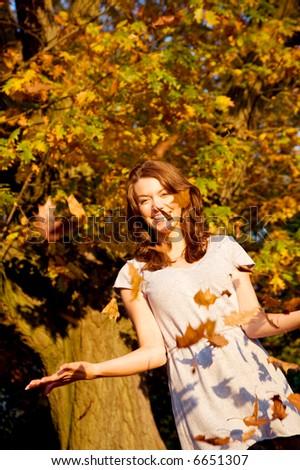 autumn girl having fun throwing leaves around at sunset time - stock photo