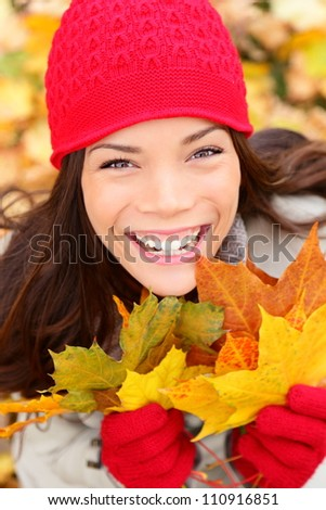 Autumn girl in fall colors smiling happy. Fall woman portrait of cheerful and beautiful mixed race Asian Caucasian young woman.