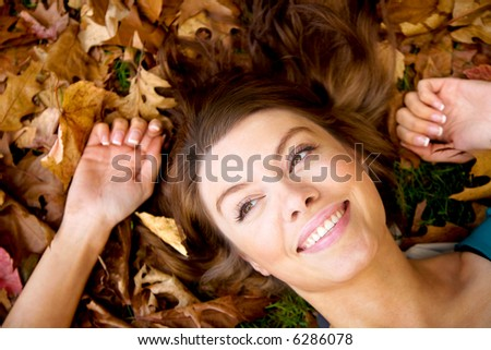 autumn girl portrait smiling and relaxing on the floor - stock photo