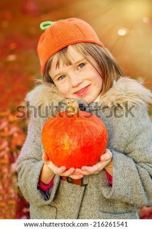 Autumn girl wearing orange hat and holding pumpkin in hands. Warm sunlight background. - stock photo