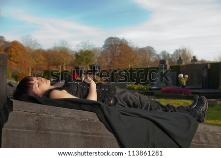 Autumn graveyard and a young gothic girl dead on a tombstone - stock photo