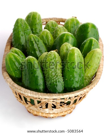 Autumn harvest cucumbers in a basket on white background