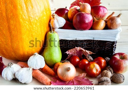 Autumn harvest of fruits and vegetables on a wooden background. Pumpkin, pears, apples, onions, garlic, carrots - stock photo