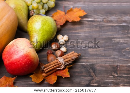 Autumn harvest. Pears, plums, apple, grapes and yellow leaves on the wooden table - stock photo