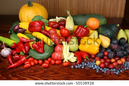 Autumn harvest - ripe vegetables and fruits. Organic produce. Tomatoes, onion, plums, pepper, raspberries, zucchini, pears and other food. - stock photo