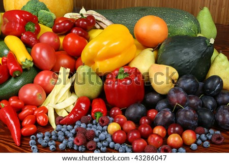 Autumn harvest - ripe vegetables and fruits. Organic produce. Tomatoes, plums, pepper, raspberries, zucchini, pears and other food. - stock photo