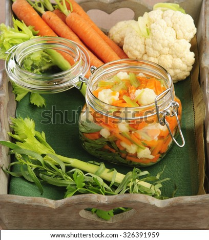 Autumn home preservation of vegetables, canned carrot cauliflower celery herb tarragon in a glass jar on a wooden tray - stock photo