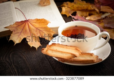 Autumn hot tea with cookies and falling leaves around.