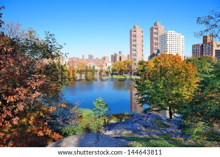 Autumn in Central Park north end in New York City Manhattan with buildings, lake and colorful foliage with clear blue sky. - stock photo