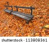 Autumn in the city. Bench on the background of autumn leaves. Background. - stock photo