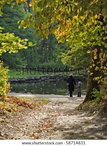 Autumn in the park with mother and daughter - stock photo