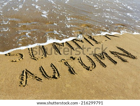 Autumn is coming concept - inscription Summer and Autumn written on a sandy beach, the wave is starting to cover the word Summer. - stock photo