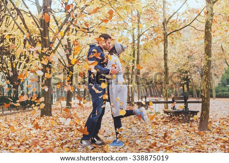 autumn kiss, young loving couple in the park with falling leaves - stock photo