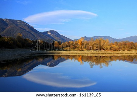 Autumn lake with mountains in the background with sky reflection