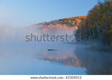 Autumn landscape at sunrise of Council Lake in fog, Michigan's Upper Peninsula, USA - stock photo