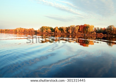 autumn landscape beautiful morning on the river, colorful trees on the beach and clouds on blue sky - stock photo