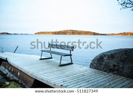 Autumn landscape. Bench on the dock. The evening near the water.