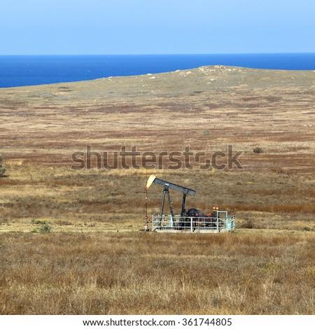 autumn landscape dirt road and Oil pump in the arid steppe Crimea - stock photo
