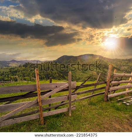 autumn landscape. fence near the meadow path on the hillside. forest in fog on the mountain. at sunset - stock photo