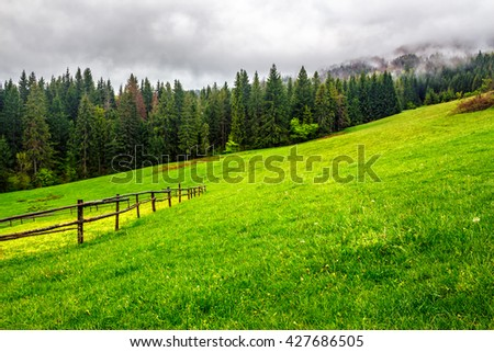 autumn landscape. fence on the hillside meadow near forest in mountain. - stock photo