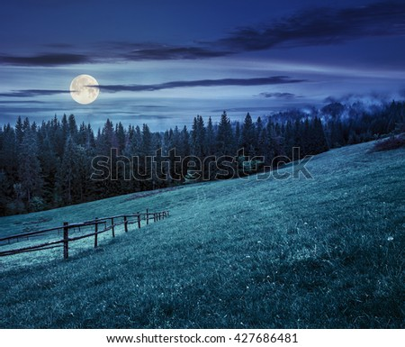 autumn landscape. fence on the hillside meadow near forest in mountain at night in full moon light - stock photo