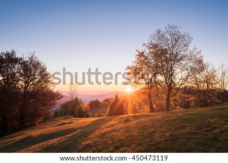 Autumn landscape in a mountain village. Beautiful sunset with a warm glow. Stacks dry hay in a meadow. Subsistence agriculture. Carpathian, Ukraine, Europe. HDR and color toning - stock photo
