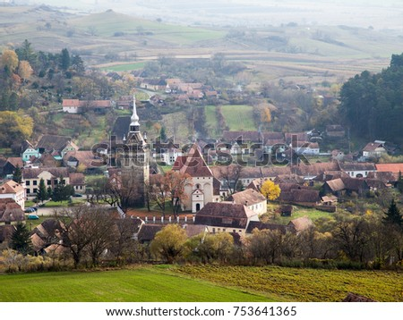 Autumn landscape in old Transylvania village dominated by fortified church