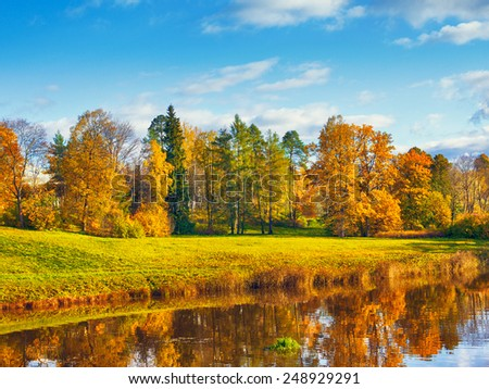 autumn landscape in park with river and blue sky - stock photo
