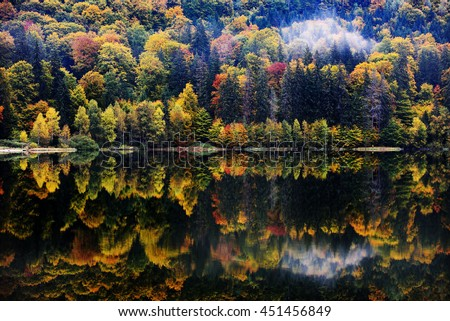 autumn landscape in the mountains with trees reflecting in the water - stock photo